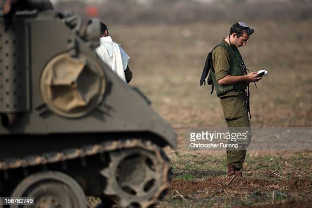 An Israeli soldier prays next to armoured personnel carriers as they wait in a staging area on November 21 2012 on Israel's border with the Gaza...
