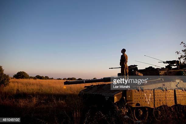An Israeli soldier prays on a Merkava tank on the Israeli-Syrian border near Quneitra on June 22, 2014 Israeli-annexed Golan Heights. An Israeli teen...