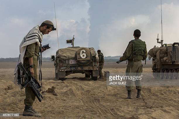 An Israeli soldier prays on the Israeli side of the border with the Gaza Strip on July 29 as smoke billows from a power plant following overnight...
