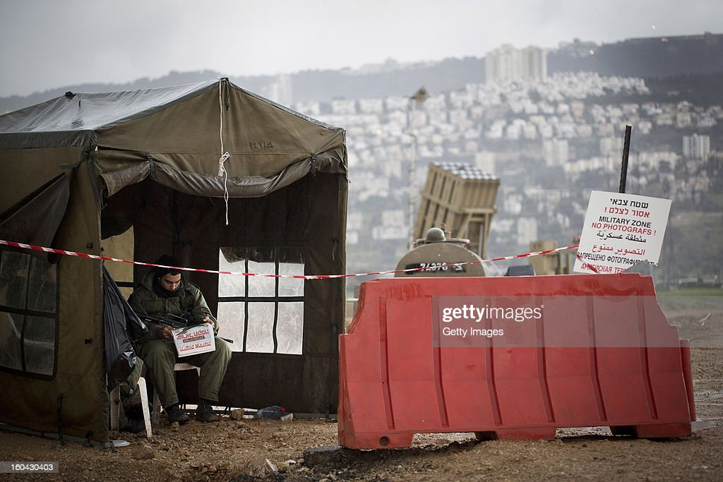 An Israeli soldier reads the newspaper next to an 'Iron Dome' short-range missile defense system on January 31, 2013 near the northern city of Haifa, Israel. The Iron Dome missile defense system is designed to intercept and destroy incoming short-range rockets and artillery shells. Israel remains on high alert to the possibility of Islamic militants getting hold of Syrian missiles and chemical weapons, with reports yesterday that the Israeli air force launched an airstrike on a convoy carrying weapons from Syria to Lebanon on the Syria-Lebanon border.