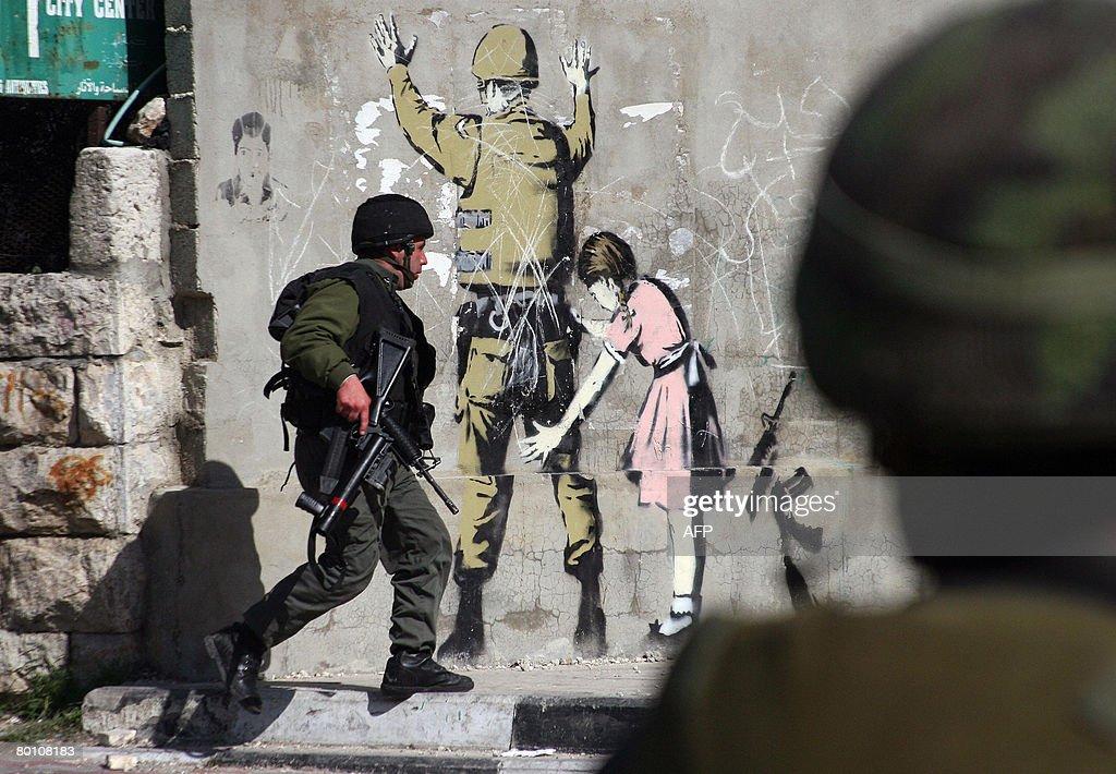 An Israeli soldier runs past a wall mura : News Photo