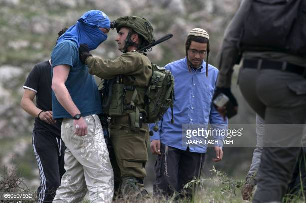 An Israeli soldier scuffles with a masked Israeli settler while trying to remove him from the area of a protest by Palestinians on March 30 to mark...