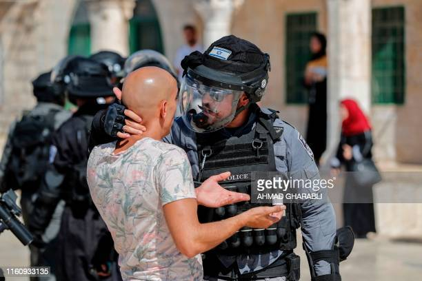 An Israeli soldier scuffles with a Palestinian at the al-Aqsa Mosque compound in the Old City of Jerusalem on August 11 as clashes broke out during...