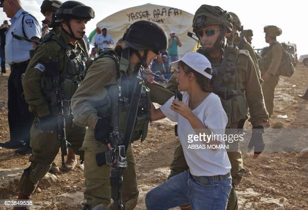 TOPSHOT An Israeli soldier scuffles with an Israeli female activist during a demonstration by Palestinians and Israelis against the construction of...