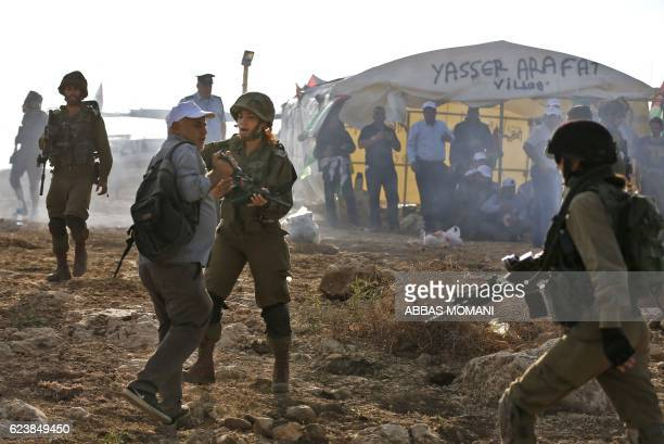 An Israeli soldier scuffles with an Palestinian journalist during a demonstration by Palestinians and Israelis against the construction of Jewish...