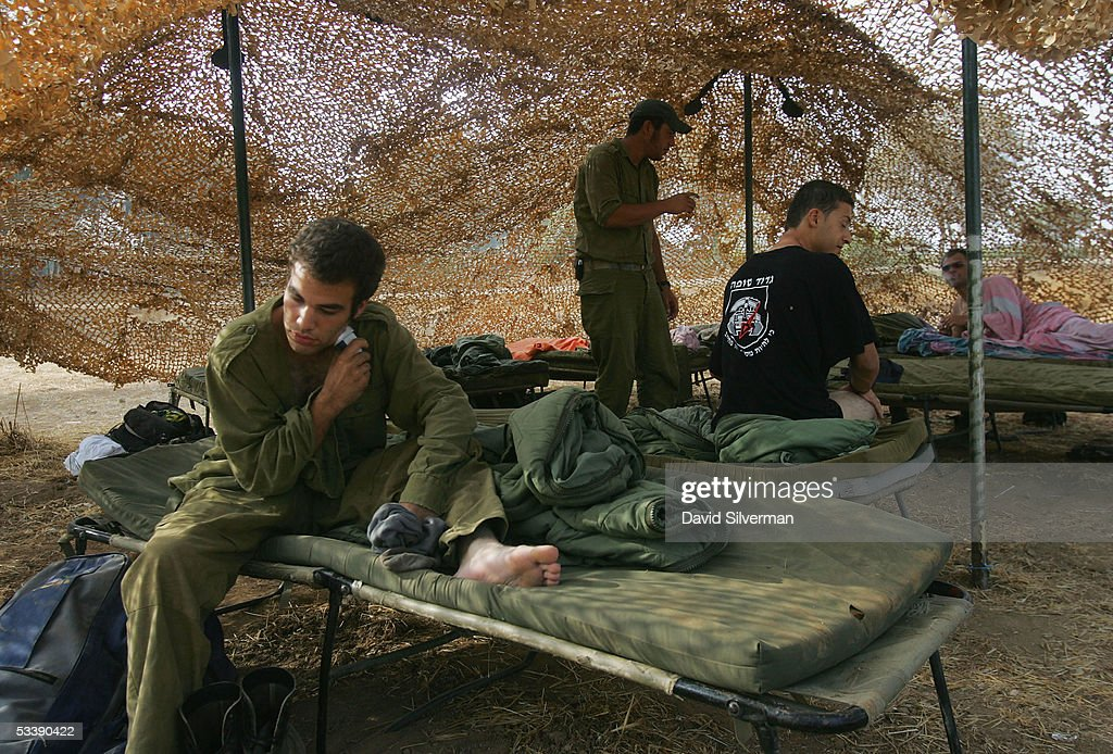 An Israeli soldier shaves as others wake up under camouflage netting near the border with the Gaza Strip August 15, 2005 in the fields of Kibbutz Mefalsim in southern Israel. The Israeli army has deployed hundreds of tanks and armored vehicles and thousands of troops to defend the Jewish state's historic withdrawal from the Gaza Strip after a 38-year occupation.