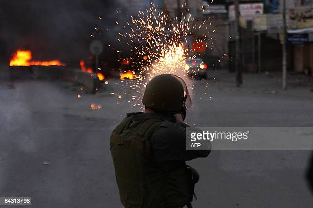 An Israeli soldier shoots tear gas at Palestinian youths during clashes that followed a protest against Israel�s offensive in the Gaza Strip at...