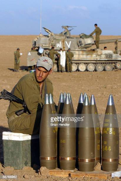 An Israeli soldier sits alongside artillery shells where his unit has deployed September 25 2005 in the fields of Kibbutz Nahal Oz on the border with...