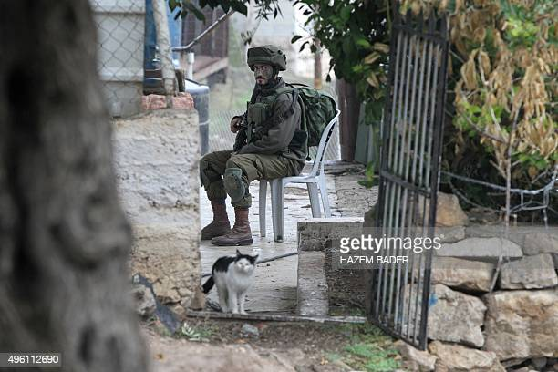 An Israeli soldier sits as security forces search Palestinian homes in the West bank town of Hebron on November 7 2015 Israeli forces blocked exits...
