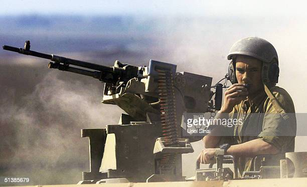 An Israeli soldier speaks on the radio onboard an armored personnel carrier APC at the border between Kibbutz Mefalsim and the Gaza Strip town of...