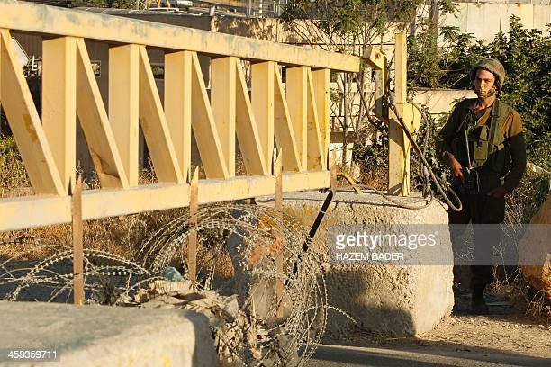 An Israeli soldier stand guard near a barrier blocking the road at a southern entrance of Hebron on July 2 after Israeli troops locked down the...