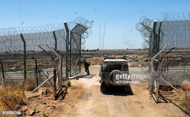 An Israeli soldier stands as an army vehicle passes by a gate at an army base along the road parallel to the border fence separating the...