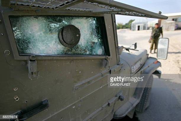 An Israeli soldier stands beside a damaged Israeli army jeep after two soldiers were lightly wounded when a roadside bomb exploded along the security...