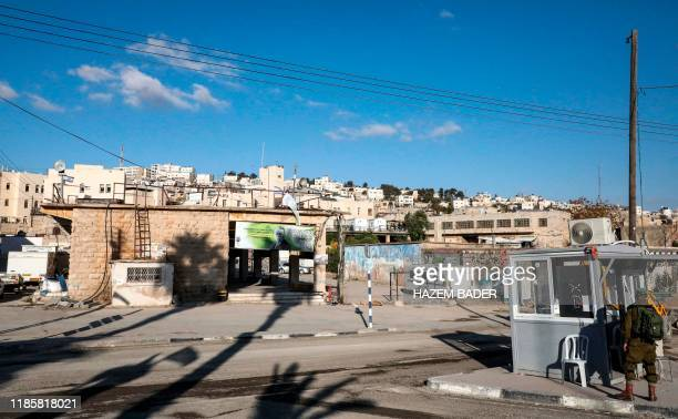 An Israeli soldier stands by an army checkpoint opposite an old market building along alShuhada street in the flashpoint city of Hebron in the...