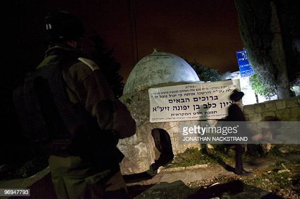 An Israeli soldier stands guard as an ultraOrthodox Jewish man arrives to pray at the tomb of Jewish biblical figure Calev ben Yefuneh in the...