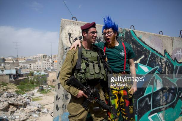 An Israeli soldier stands guard as Israelis take part in a parade celebrating the Jewish holiday of Purim on March 12 2017 in Hebron West Bank Purim...