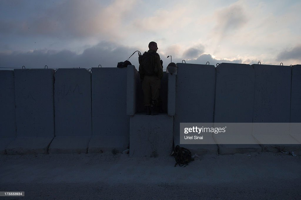 An Israeli soldier stands guard as Palestinian Muslim worshippers cross the Qalandia checkpoint on their way to Jerusalem on July 12, 2013 near Ramallah, West Bank. Thousands of Palestinian worshippers crossed from the West Bank into Israel to attend the first Friday prayers of Ramadan at the the Al-Aqsa mosque compound in Jerusalem.