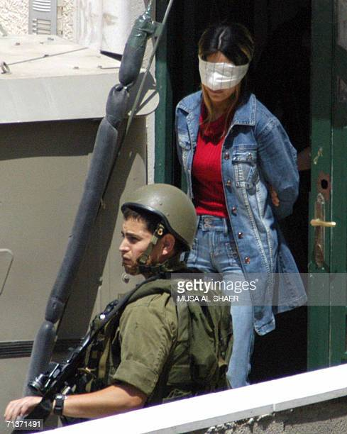 An Israeli soldier stands guard as Palestinian woman Sherin Mohammed Abu Kamel a member of the former ruling Fatah party is blind folded and taken...