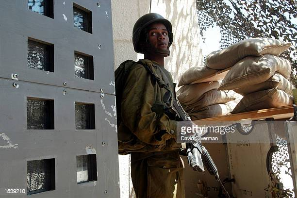 An Israeli soldier stands guard at the door of the Bethlehem Peace Center the complex on Manger Square which was taken over by the Israeli army as...