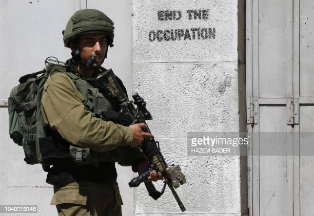 An Israeli soldier stands guard during a planned tour by religious Israelis in the divided city of Hebron to visit the tomb of Biblical figure...