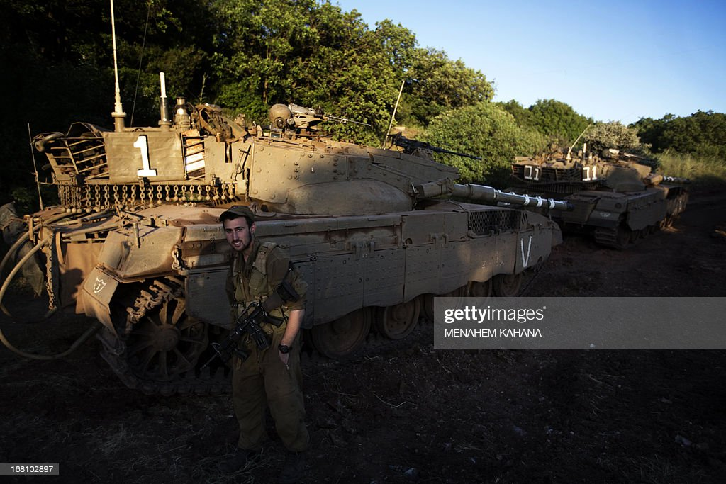 An Israeli soldier stands guard next to Merkava tanks in the Israeli annexed Golan Heights near the border with Syria on May 5, 2013. Israel carried out a pre-dawn air strike near Damascus, targeting Iranian missiles destined for Lebanon's Hezbollah in the second such raid on Syria in three days, a senior Israeli source said.