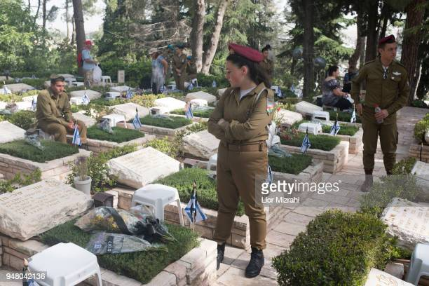 An Israeli soldier stands next to graves at the military cemetery on April 18 2018 in Jerusalem Israel Israel marks the Remembrance Day to...