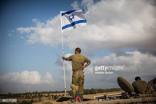 An Israeli soldier stands on top of an armored personnel carrier near the Israeli-Gaza border on July 15, 2014 near Sderot, Israel. As operation...