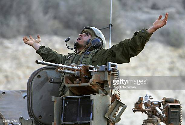 An Israeli soldier stretches as he prepares to disembark from an armored personnel carrier on his return from an early morning patrol in southern...