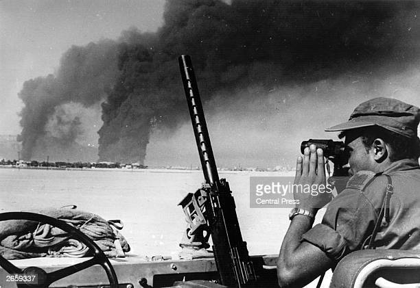 An Israeli soldier studies an oil refinery at Port Suez set alight by Israeli shelling during the SixDay War He views it from the other side of the...