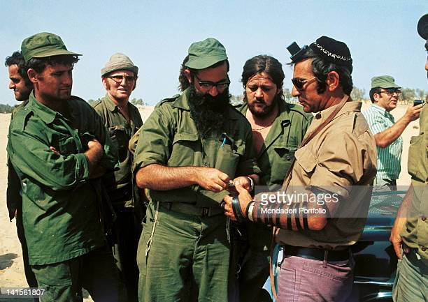 An Israeli soldier surrounded by his fellow soldiers wears the phylactery rites in his left arm to be ready for the morning prayers October 1973