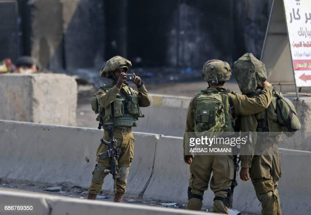 An Israeli soldier takes a picture of his comrades during a protest by Palestinians in support of prisoners refusing food in Israeli jails for more...