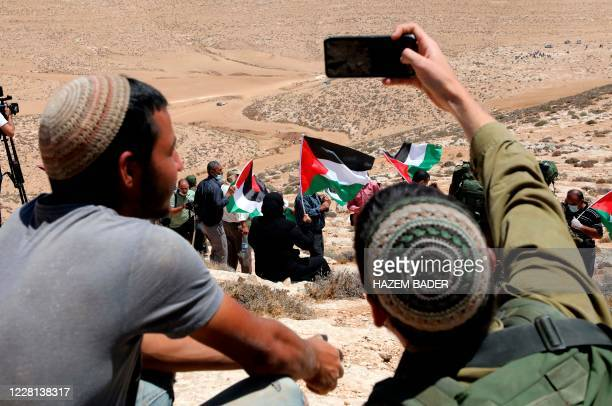 An Israeli soldier takes a selfie of himself with a settler, as Palestinian landowners and demonstrators protest Israeli settlement building...