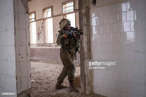 An Israeli soldier takes aim as male and female combat soldiers of the Bardales battalion take part in a long day of practise in a heavy fog on July...