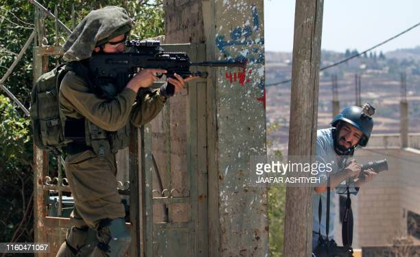 An Israeli soldier takes aim at Palestinian protesters while a photojournalist takes cover during clashes following a weekly protest against the...