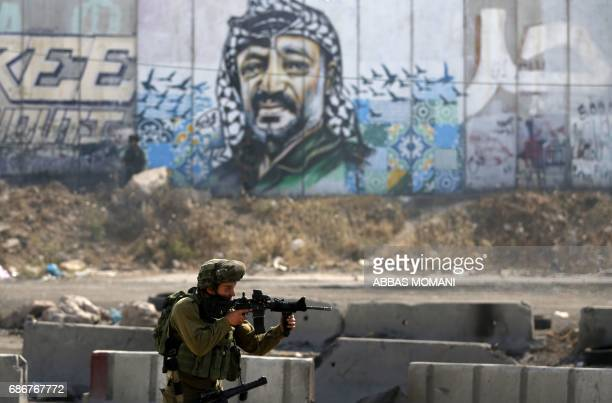 An Israeli soldier takes an alert position in front of a mural portrait of late Palestinian leader Yasser Arafat during a protest by Palestinians on...