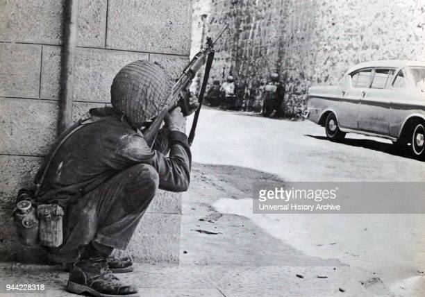 An Israeli soldier takes cover during Street to street fighting in Jerusalem during the Six Day War