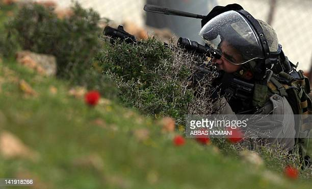 An Israeli soldier takes position during a weekly demonstration by Palestinians in the West Bank village of Nabi Saleh against the expansion of...