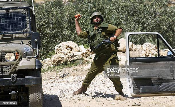 An Israeli soldier throws a stun grenade at Palestinians demonstrating against Israels separation barrier on June 21 2004 at the Palestinian village...