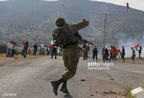 TOPSHOT An Israeli soldier throws teargas against Palestinian protesters during a protest against Jewish settlements on November 24 in the Jordan...