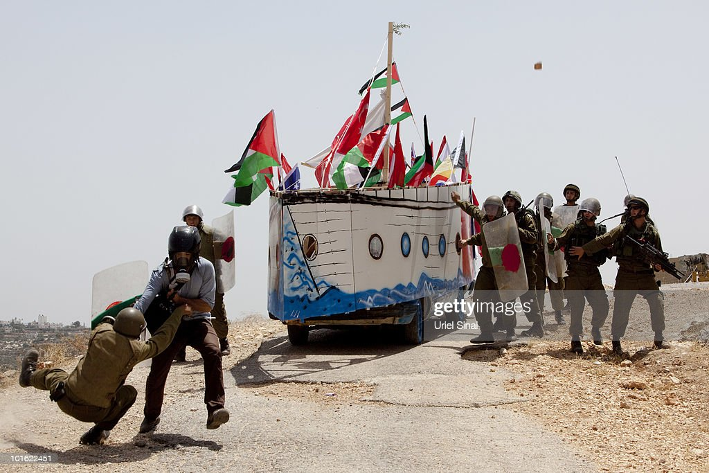 An Israeli soldier tries to arrest a journalist as Palestinian protesters use a replica of the Gaza aid flotilla near an Israeli barrier, as they object to Israel's attack on the flotilla earlier this week, on June 4, 2010 in Bil'lan, the West Bank. Israel has faced international criticism over the deadly raid on May 31, aboard a ship carrying humanitarian aid to the Gaza Strip.