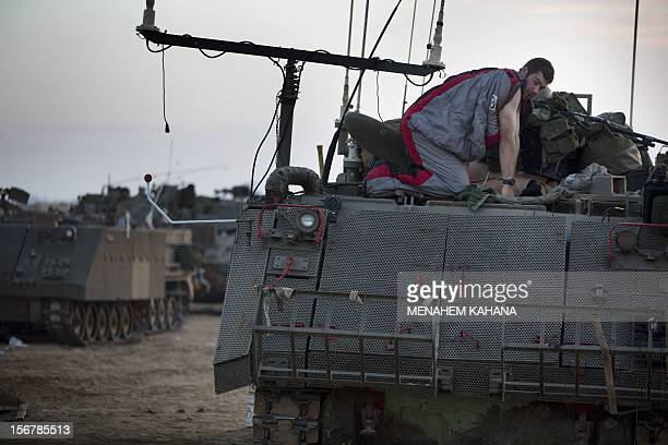 An Israeli soldier wakes up after spending a night sleeping on top of an armoured personnel carrier at an Israeli army deployment area near the...