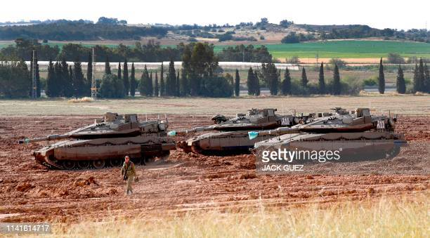 An Israeli soldier walks in front of a Merkava tanks, stationed near the border with the Gaza Strip in southern Israel on May 6, 2019. - Palestinian...