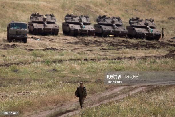 An Israeli soldier walks next to Merkava tanks deployed near the Israeli-Syrian border on May 10, 2018in the Israeli-annexed Golan Heights. Some 20...
