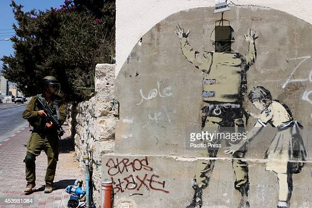 An Israeli soldier walks past a Banksy graffitti mural in Bethlehem. The Islamic Jihad faction organized protests in solidarity with Gaza, in the...