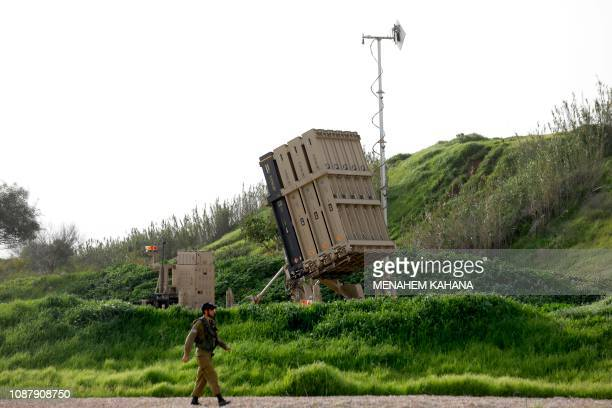 An Israeli soldier walks past a battery of the Iron Dome defence system, designed to intercept and destroy incoming short-range rockets and artillery...