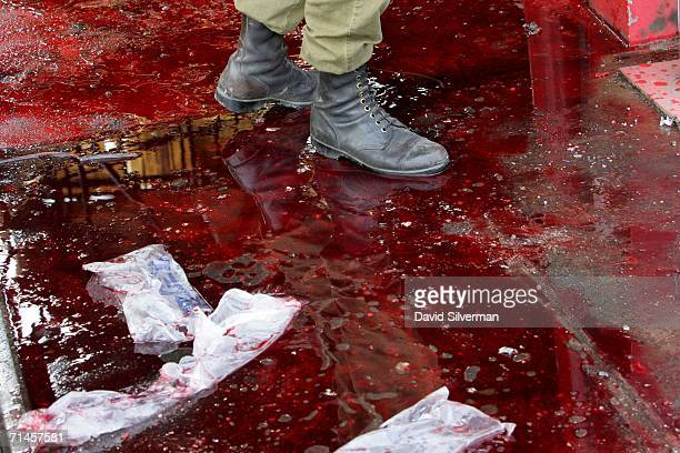 An Israeli soldier walks through a pool of blood that covers a railway platform where a Hezbollah missile struck a railways depot July 16 2006 in the...
