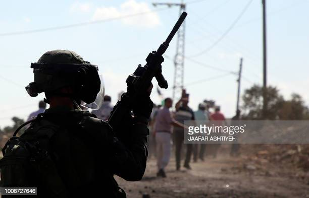 An Israeli soldier watches during clashes with Palestinian demonstrators following a weekly demonstration against the expropriation of Palestinian...