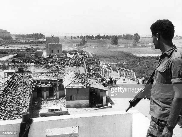 An Israeli soldier watches Palestinian refugees crossing the warwretched Allenby Bridge to reach the east bank of the Jordan 22 June 1967 After...