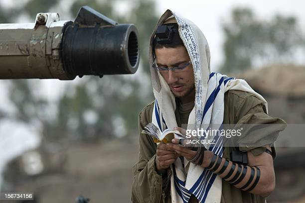 An Israeli soldier wearing a 'Talit' and a 'Tefilin' reads his morning prayers at an Israeli army deployment area near the IsraelGaza Strip border as...