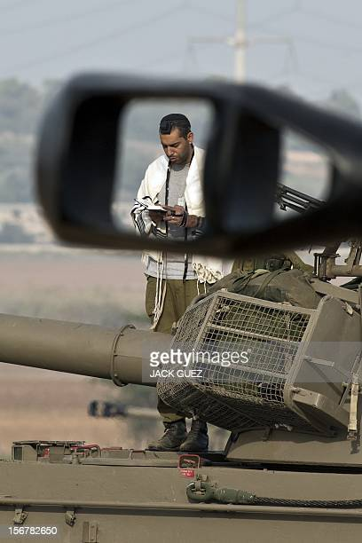 An Israeli soldier wearing a 'Talit' and 'Tefilin' performs morning prayers near his Israeli 155mm artillery canon at an Israeli army deployment area...